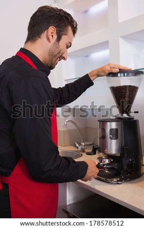 Happy barista grinding coffee beans in a cafe