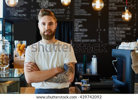 Happy barista standing at trendy coffee shop, cafe - small business concept