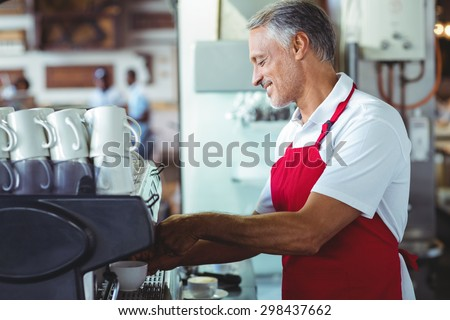 Happy barista using the coffee machine at the cafe - stock photo