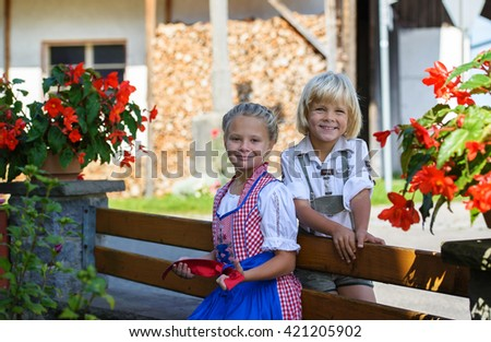 Happy bavarian boy with sister  on the farm in Germany . - stock photo