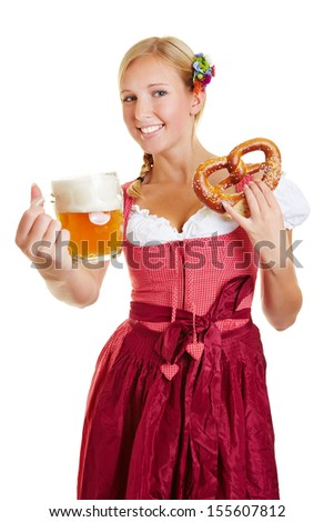 Happy bavarian woman in a dirndl with pretzel offering mug of beer