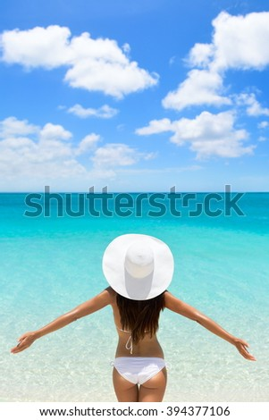 Happy beach vacation carefree woman on luxury tropical getaway destination wearing a white sun hat from behind with arms raised in freedom.  Person from behind with slim body. Happiness and success. - stock photo