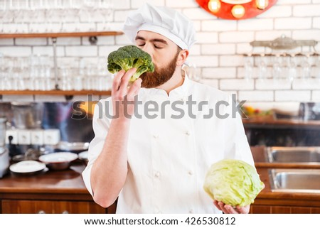 Happy bearded chef cook smelling fresh broccoli on the kitchen - stock photo