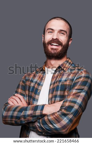 Happy bearded man. Handsome young bearded man keeping arms crossed and smiling while standing against grey background - stock photo