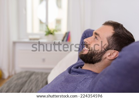 Happy bearded man relaxing at home daydreaming sitting back on the sofa with his hands behind his head and a big contented smile , side view