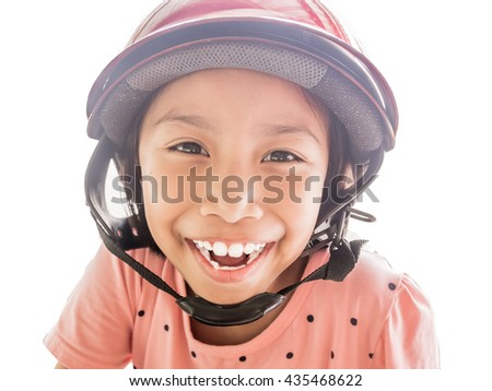 Happy Beautiful asian kids wear red safety helmet with her smile. Asian kids riding motorcycle outdoors. Safety concept. - stock photo