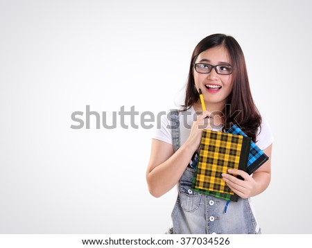 Happy beautiful Asian school girl looking up to copy space with cheerful face, over white background - stock photo