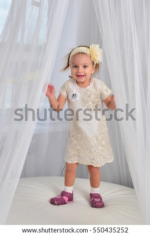 Happy beautiful baby girl in white dress