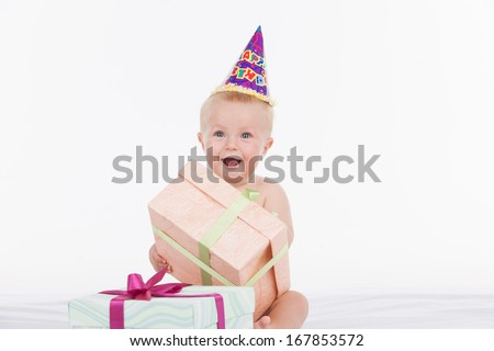 Happy beautiful baby in party hat holding present box. Sitting isolated over white background  - stock photo
