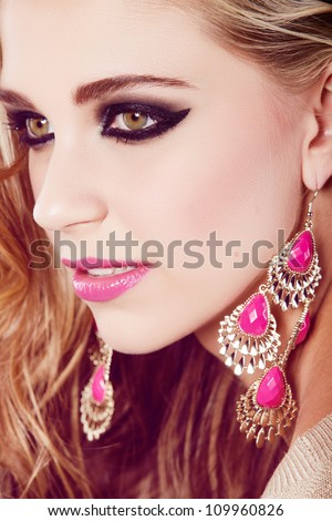 happy beautiful blond girl with curly long hair and smoky eyeshadow makeup wearing neon pink and gold earrings - stock photo