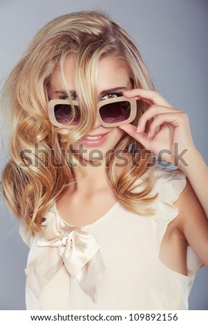 happy beautiful blond girl with curly long hair wearing pastel beige silk blouse and smiling behind fashion sunglasses - stock photo