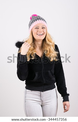 Happy beautiful blonde teenage girl in black sweatshirt, denim jeans, and knitted beanie hat laughing. Vertical, mild retouch, candid studio shot. - stock photo