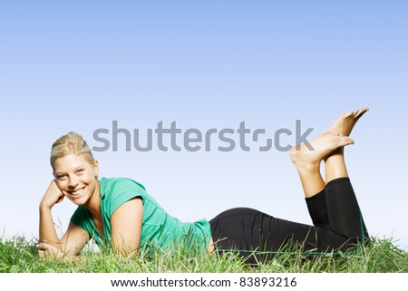 Happy beautiful blonde woman lying on green grass.