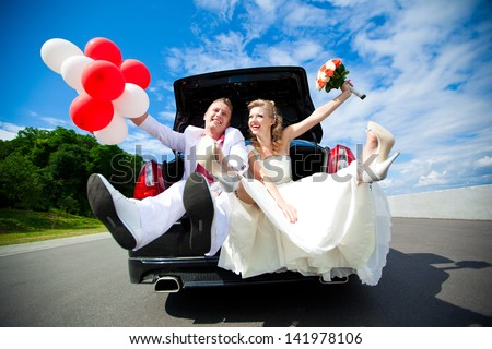 Happy beautiful bride and groom sitting in the trunk of a car. Honeymoon, fun and laughter. - stock photo