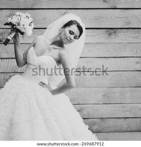 Happy beautiful brunette bride in white wedding dress with hairstyle posing against wood background.  - stock photo
