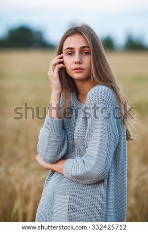 happy beautiful brunette smiling girl posing in wheat field at sunset, wearing knitted dress - stock photo