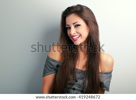 Happy beautiful brunette woman with long hair looking with toothy smiling on blue background