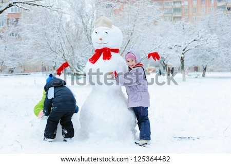 Happy beautiful children building snowman in garden - stock photo