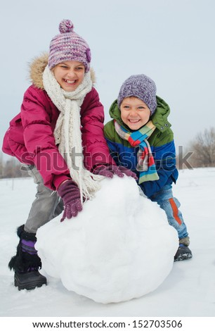 Happy beautiful children building snowman outside in winter time - stock photo