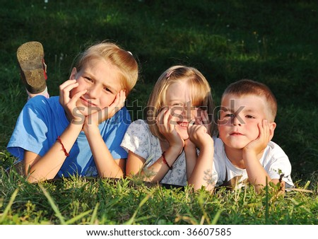 Happy beautiful children laying on ground outdoor - stock photo