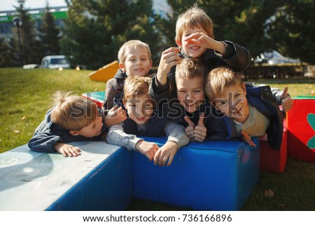 Happy beautiful children to have fun together on the Playground, Looking at the camera lying on her stomach