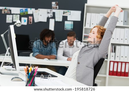 Happy beautiful contented young businesswoman relaxing in her chair stretching her arms in the air in a busy office with multiethnic male business partners - stock photo
