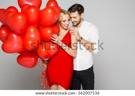 Happy beautiful couple looking at each other and holding balloons heart. Valentine's day. - stock photo