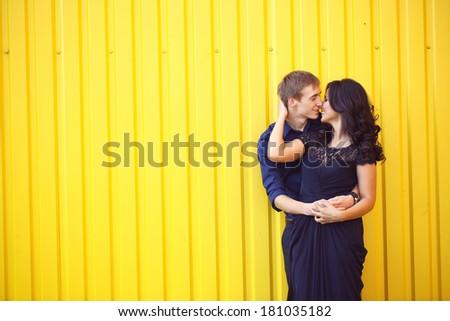 Happy beautiful couple on a yellow wall - stock photo