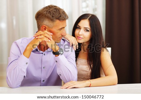 Happy beautiful couple sitting at the table at home - stock photo