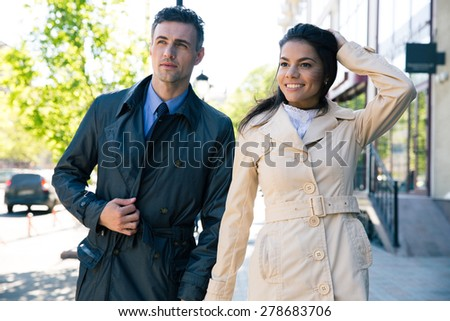 Happy beautiful couple walking on the city street - stock photo