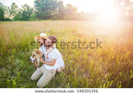 Happy beautiful couple with their Alabai dog in nature with sunset.