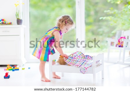 Happy beautiful curly toddler girl in a pink dress playing with her teddy bear putting him in a toy bed to sleep in a sunny room with big garden view windows and white furniture - stock photo