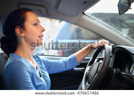 Happy beautiful curly woman in blue dress drives car in city