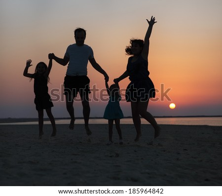 Happy beautiful family jumping on the beach at the sunset time - stock photo