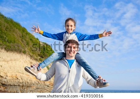Happy beautiful family man father and girl kid child having fun on beach on background of sky and mountain, girl sitting on man's shoulders - stock photo