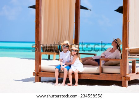 Happy beautiful family relaxing at beach during summer vacation - stock photo