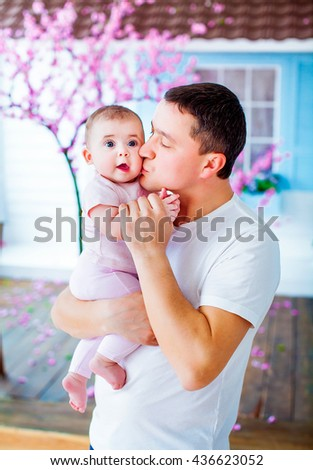 Happy beautiful father holding baby charming daughter at the hands and kisses her on the cheek, on the background of cherry blossoms. Happy childhood. Background, macro, closeup - stock photo