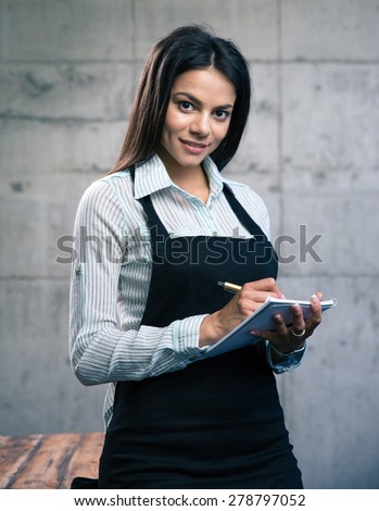 Happy beautiful female waiter in apron writing order. Looking at camera - stock photo