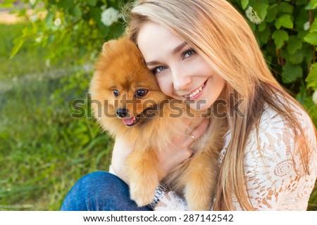 Happy beautiful gentle girl hugging her pet dog red Spitz - stock photo