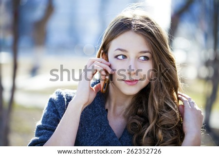 Happy beautiful girl calling by phone in spring park - stock photo