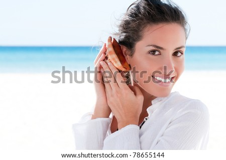 Happy beautiful girl holding and hearing a shell in a tropical beach - stock photo