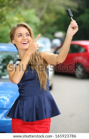 Happy beautiful girl holding car key and points a finger at it - stock photo