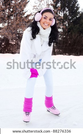 happy beautiful girl  ice skating outdoor on a warm winter day - stock photo