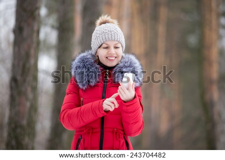Happy beautiful girl in knitted hat and red winter coat, outdoors, using mobile phone, touches the screen of smart phone, texting - stock photo