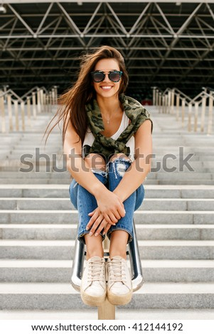 Happy beautiful girl in trendy fashion sunglasses and casual clothes sitting on a railing, have fun and smiling to the camera. Young sexy lady enjoying summer day near business or sport building. - stock photo