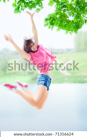 Happy beautiful girl jumping against the lake