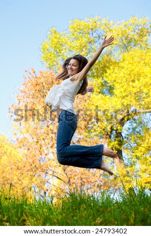 Happy beautiful girl jumping of joy on a fall day - stock photo