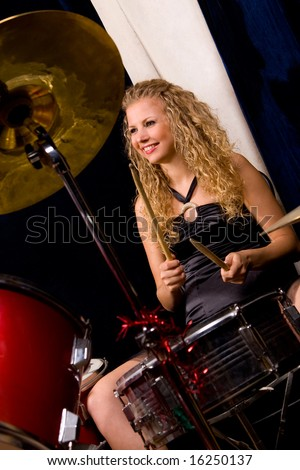 Happy beautiful girl sitting at percussion kit