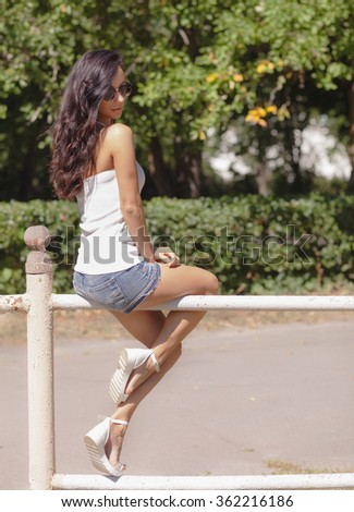 Happy beautiful girl with long dark hair and derk glasses sitting in the green park on a sunny summer day in white shirt and denim shorts