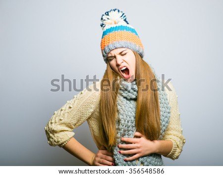 Happy beautiful girl yawns funny, knit cap, winter concept, photo studio, portrait of a woman isolated on gray background - stock photo